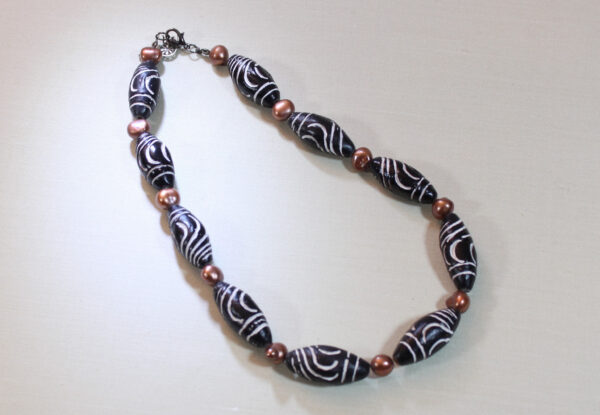 Necklace - carved black clay & orange pearls